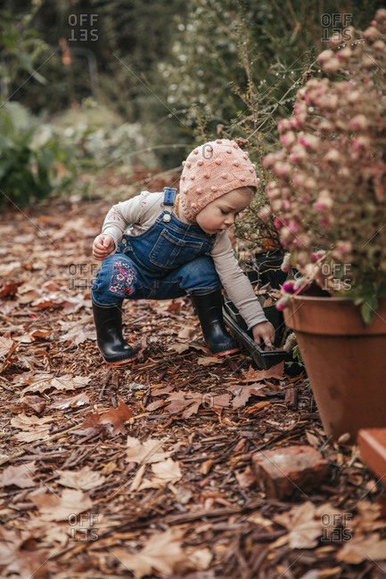 Toddler in overalls and rainboots squatting down