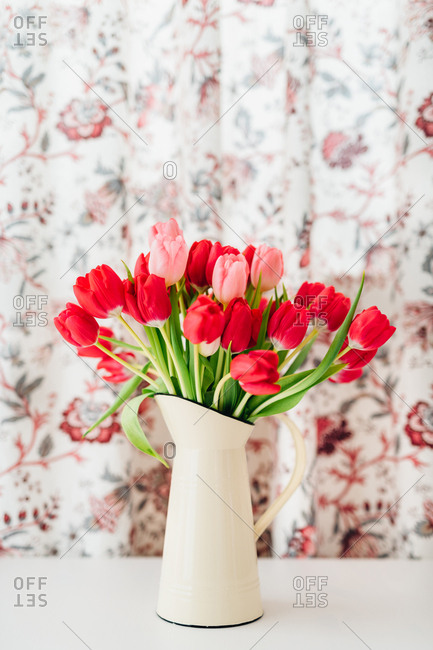 Red and pink tulips in pitcher against floral background