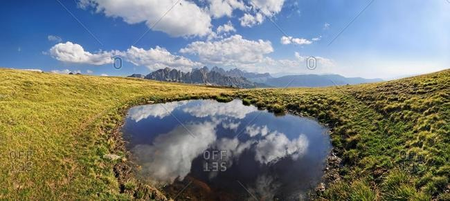 Clouds being reflected in a pond on Aferer Alm alp on Plosen mountain, view of Aferer Geisler Massif and Peitlerkofel mountain, Wuerzjoch ridge, Villnoesstal valley, Dolomites, province of Bolzano-Bozen, Italy, Europe