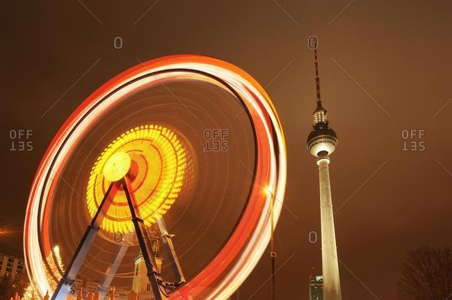 Ferris wheel in motion with TV Tower, Alexanderplatz, Berlin, Germany, Europe