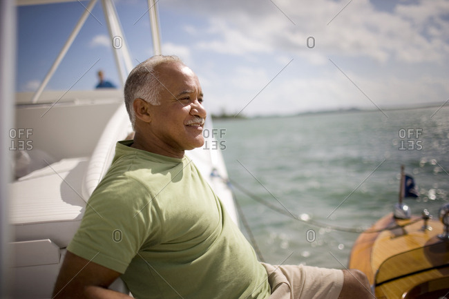 Smiling mature man sitting in his boat.