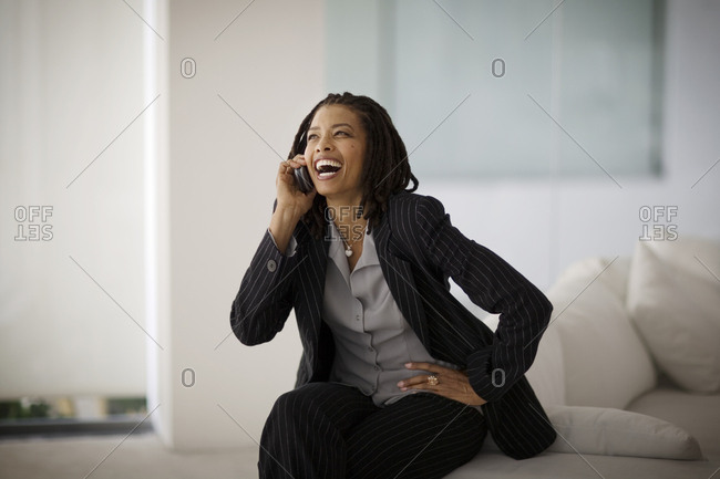 Laughing mid-adult business woman talking on a cellphone while sitting on a couch.