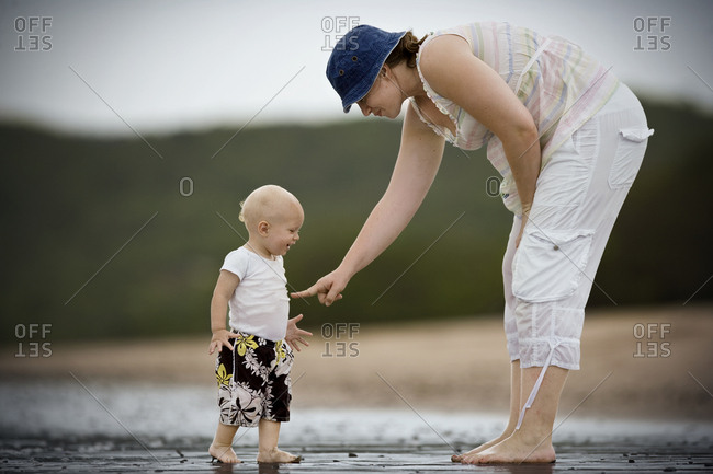 Young toddler at the beach with his mother.