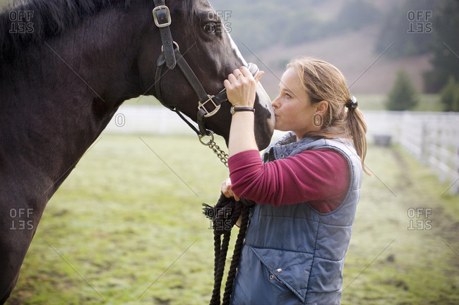 Young woman standing in a paddock with her horse.