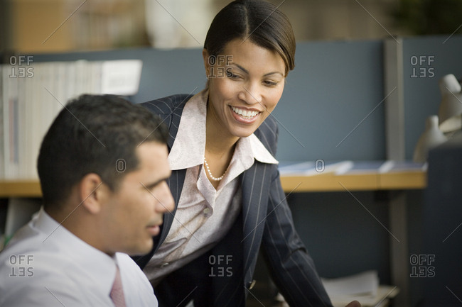 Mid-adult business woman talking with a male colleague in an office.