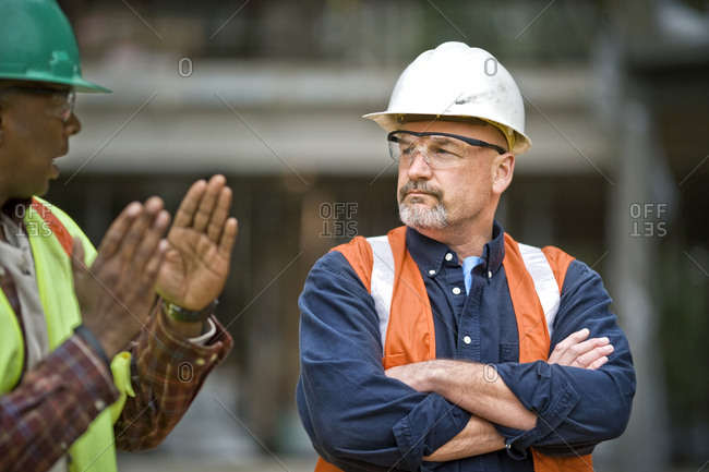 Mature male construction worker listening to a mid-adult male co-worker at a building site.