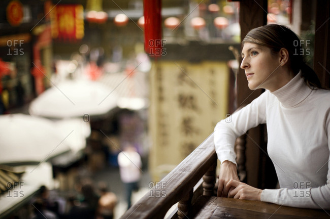 Young adult woman sitting at a table overlooking a town.
