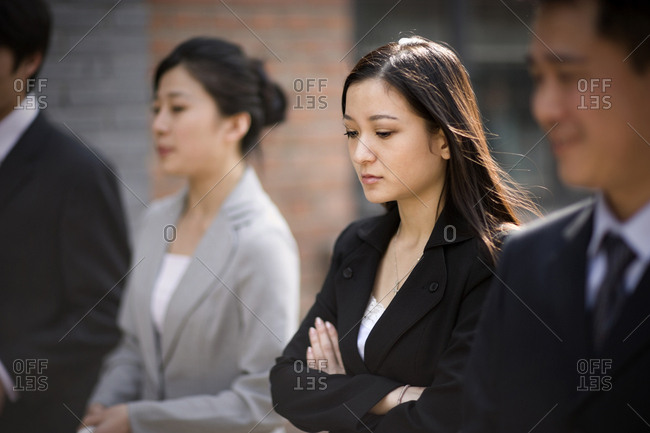 Young adult business woman walking with colleagues down a street.