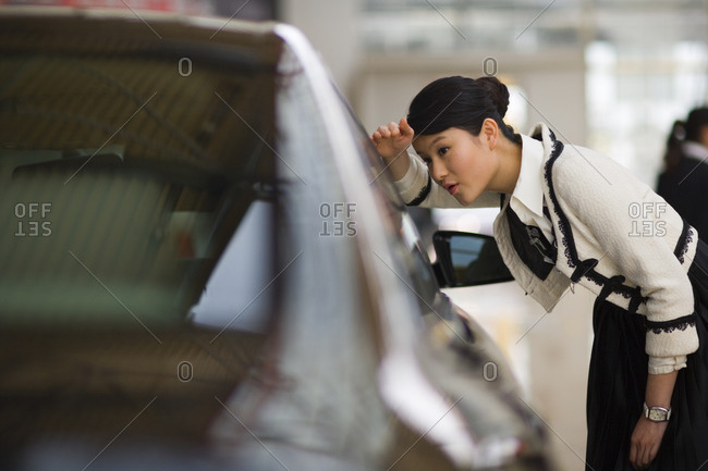 Young adult wife looking through the window of a car.