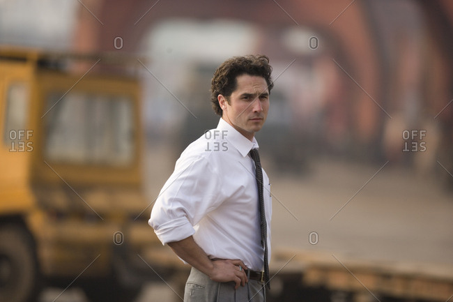 Portrait of a young adult businessman standing in a shipping yard.