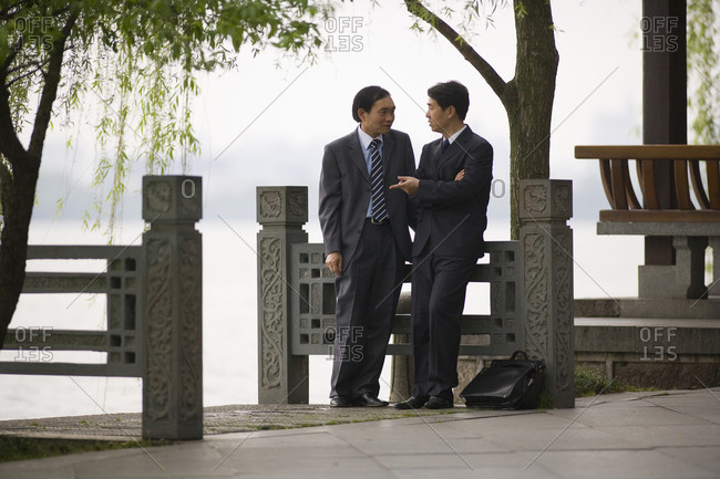 Two well-dressed businessman having a conversation  near the waterfront.