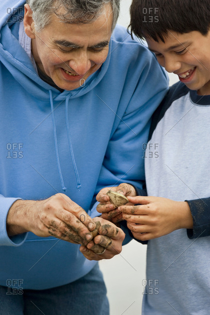 Father and son holding shellfish on the beach