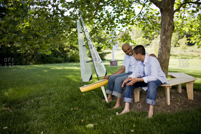 Father and son sitting on bench with model boat