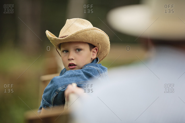 Young boy wearing a cowboy hat leans on the fence at a ranch and listens to his father tell him about the horses.