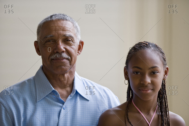 Portrait of a senior man standing next to his granddaughter.