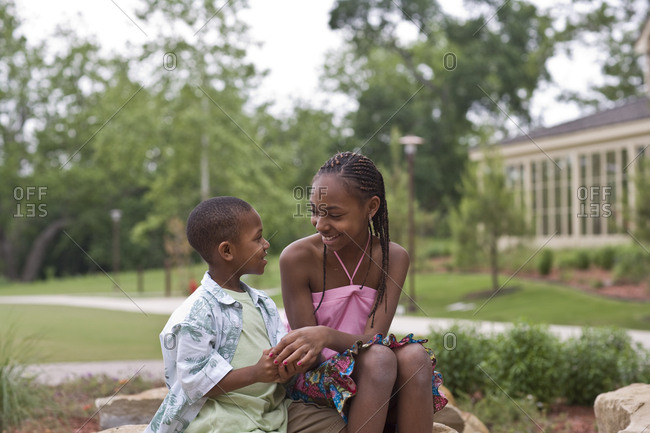 Teenage girl and her younger brother smiling at each other while sitting in a park.
