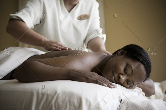 Content mid adult woman lying on a massage table with her eyes closed while being massaged by a therapist.