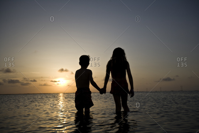 Silhouette of a brother and sister holding hands while walking in the shallows on a beach at sunset.