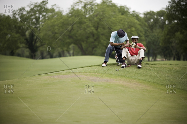 Men sitting on golf course with score card