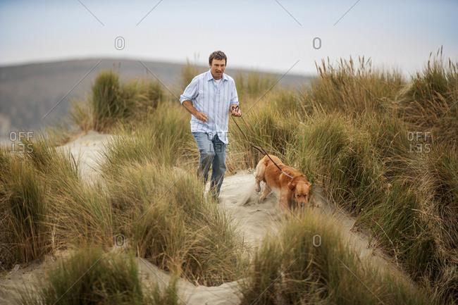 Mid adult man walking dog at beach.