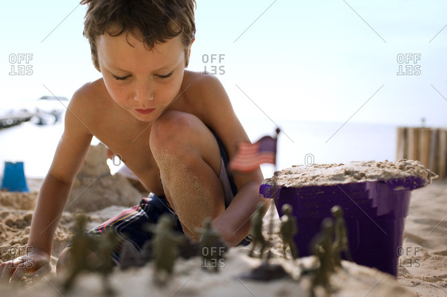 Young boy building sandcastles and playing with toys on a beach.