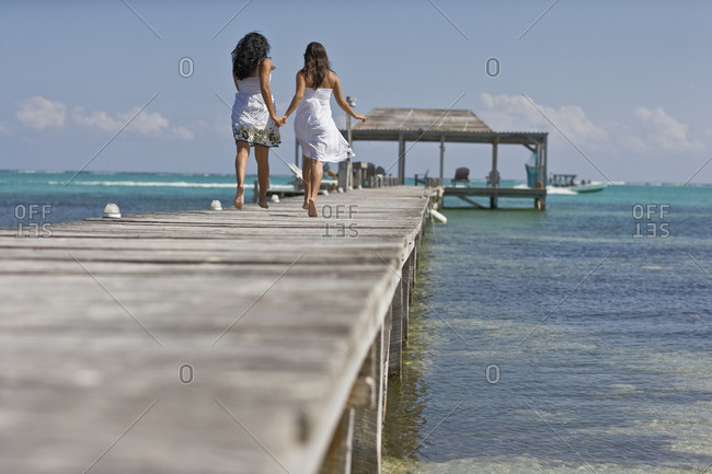 Two young adult girls running along a jetty by the beach.