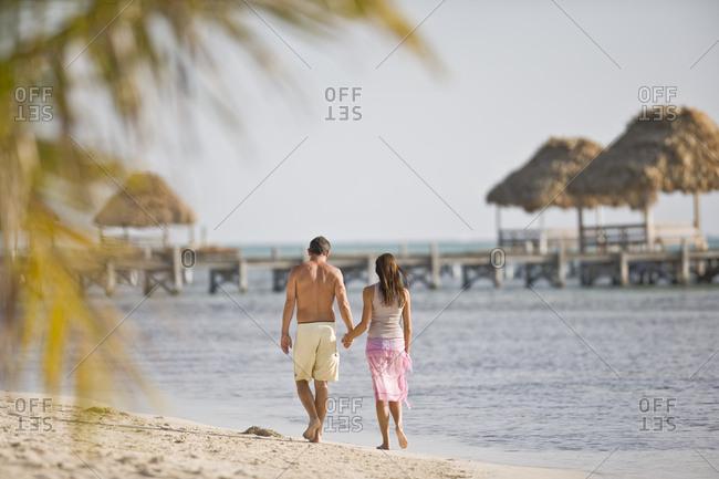 Mid-adult couple walking along a beach.