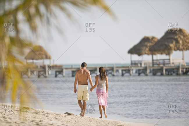 Mid-adult couple walking along a beach.