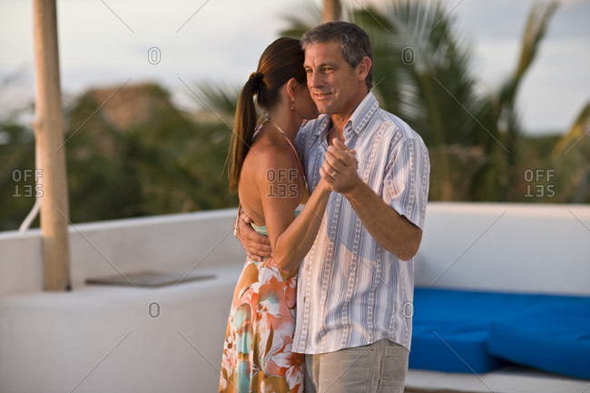 Mid-adult man dancing close with his wife on an outdoor balcony.