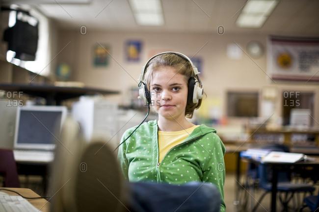 Portrait of a teenage girl in a classroom wearing headphones.