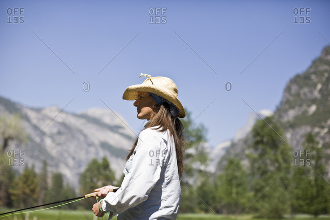 Mid-adult woman fly fishing.