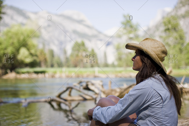 Mid-adult woman sitting with her arms around her legs beside a river.