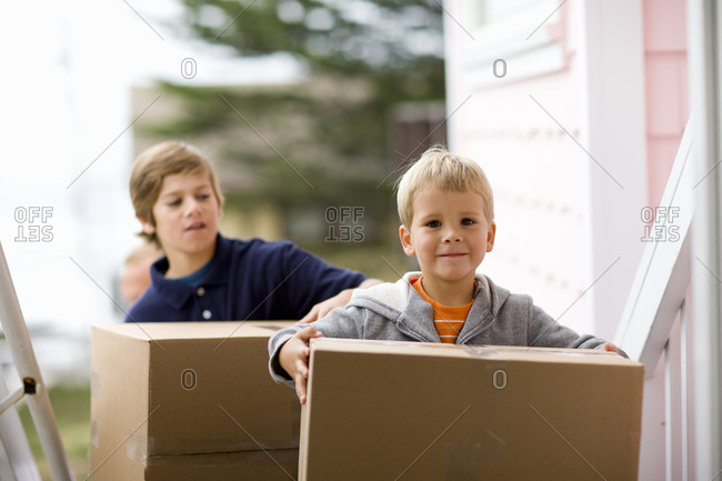 Young boy carrying boxes with his brother into a house.