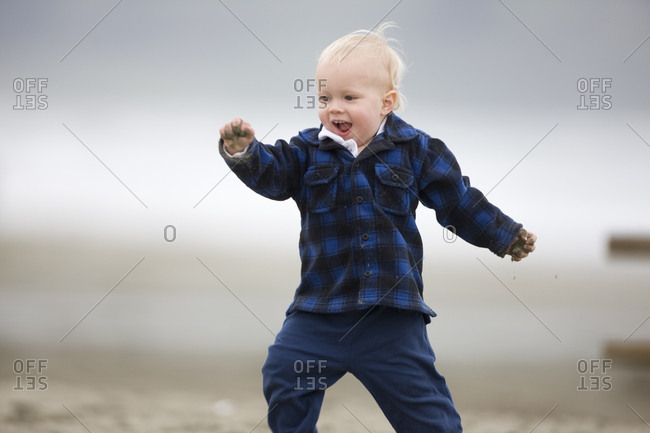 Toddler playing in the sand at a beach.