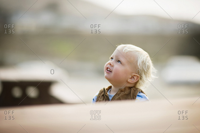 Young toddler looking upwards while outdoors.