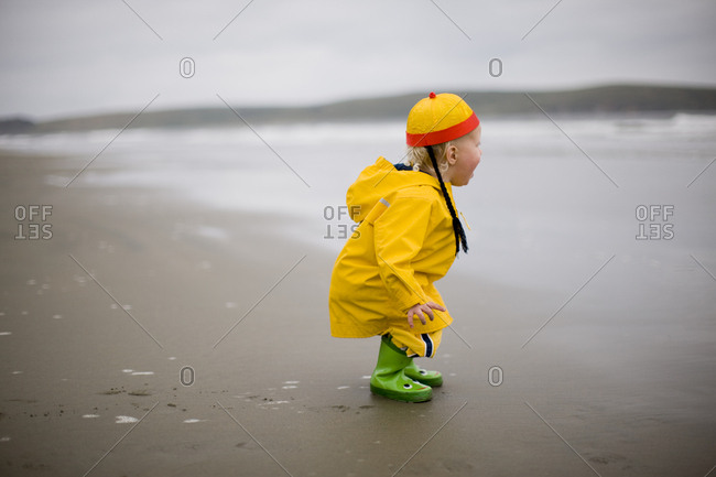 Young boy in a yellow raincoat at the beach