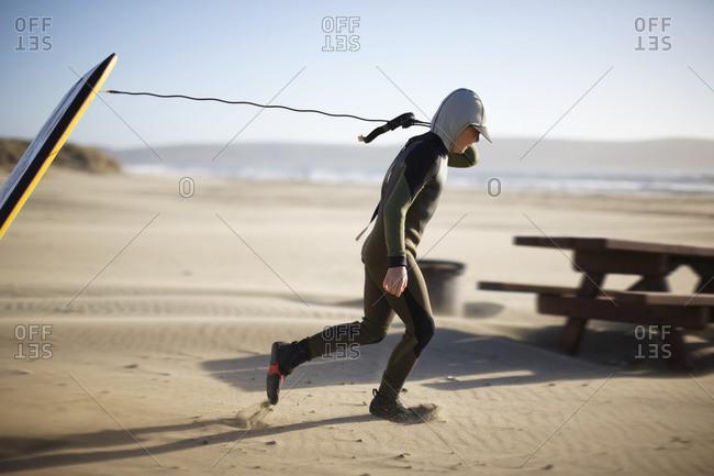 Boy wearing a wet suit pulling a boogie board along a beach.