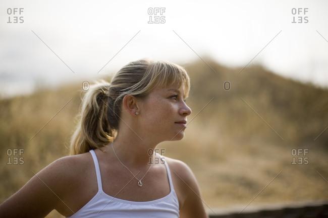Teenage girl wearing sports gear in a field outside.
