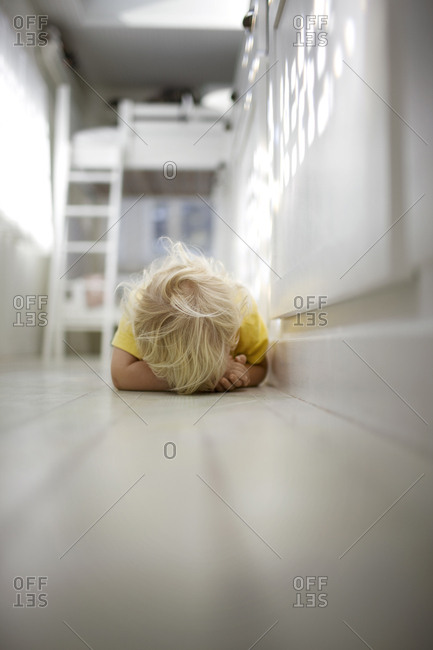 Young boy lying on the floor and hiding his face.