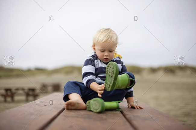 Toddler taking off rubber boots outside.
