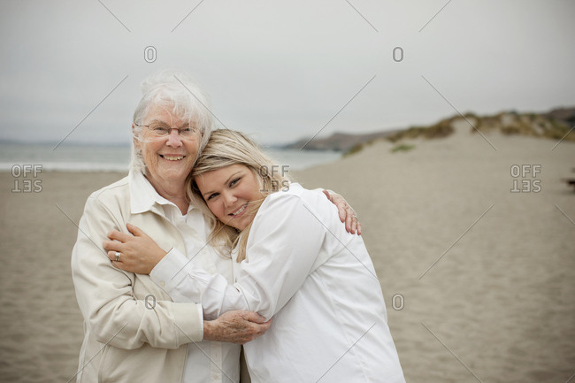 Portrait of a smiling young woman hugging her grandmother on a sandy beach.