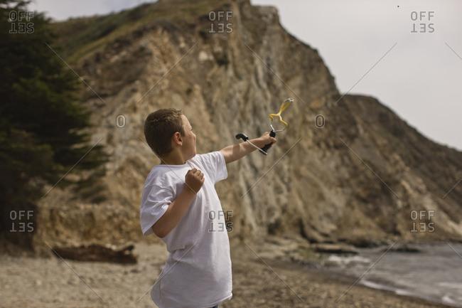 Boy shooting slingshot on the beach