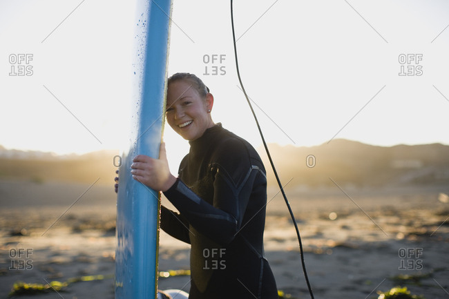 Young woman at the beach wearing a wetsuit and carrying a surfboard