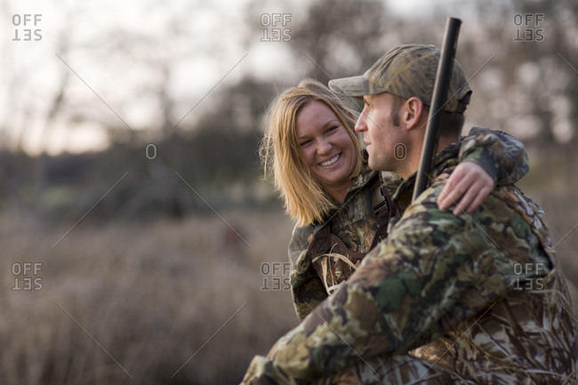 Happy couple wearing camouflage clothing.