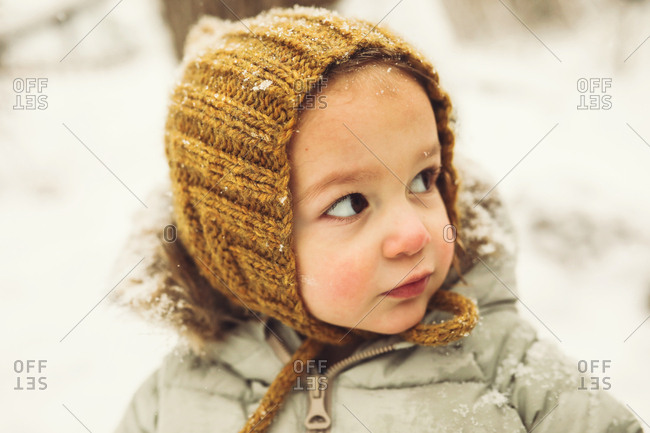 Cute toddler in a knitted hat in the snow