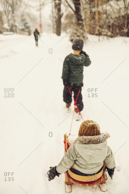Older brother pulling sibling on a sled in a snow storm