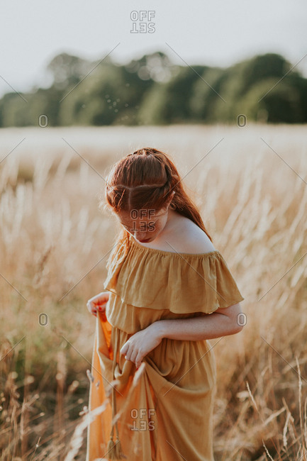 Young teen redhead girl walking in a field at sunset