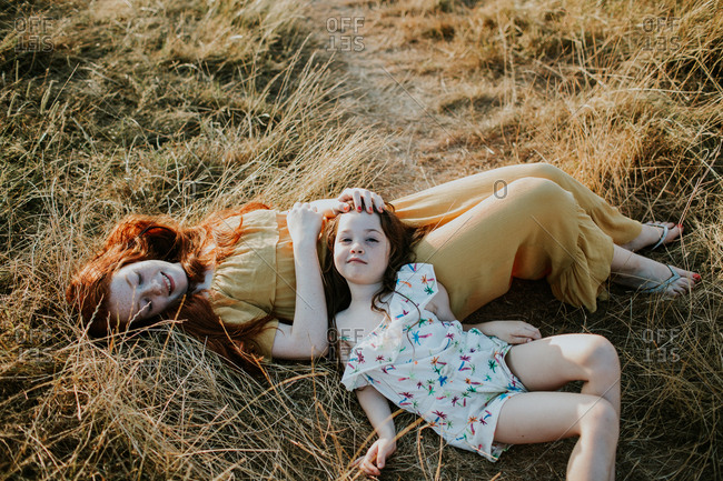 Little girl resting on her big sister's tummy in a field