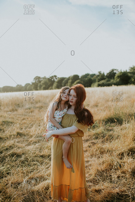 Red haired girl carrying her little sister in a field