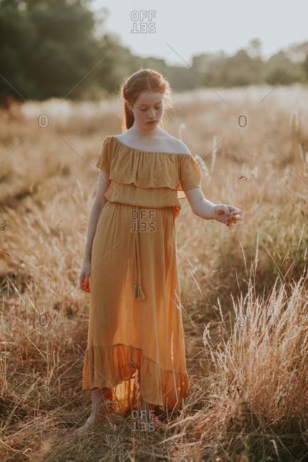 Red haired teen redhead girl walking in a field at sunset